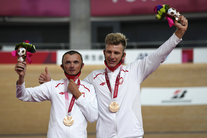 PolandÅfsÅf Marcin Polak, left, and his pilot Michal Ladosz pose with their bronze medal during the victory ceremony for the Cycling Track menÅfs B 4000m Individual Pursuit, at the Tokyo 2020 Paralympic Games, Wednesday, Aug. 25, 2021, in Izu, Shizuoka prefecture, Japan. (AP Photo/Shuji Kajiyama)