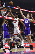 Miami Heat forward Justise Winslow, center, goes to the basket between Sacramento Kings' Willie Cauley-Stein, left, and Nemanja Bjelica during the first quarter of an NBA basketball game Friday, Feb. 8, 2019, in Sacramento, Calif. (AP Photo/Rich Pedroncelli)