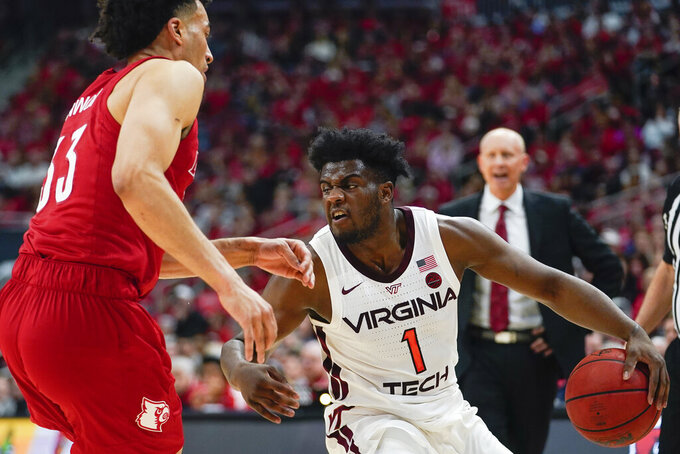 Virginia Tech guard Isaiah Wilkins (1) dribbles around Louisville forward Jordan Nwora (33) during the first half of an NCAA college basketball game, Sunday, March 1, 2020, in Louisville, Ky. (AP Photo/Bryan Woolston)