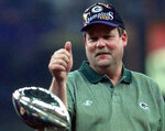 FILE - In this Jan. 26, 1997, file photo, Green Bay Packers coach Mike Holmgren gives a thumbs up behind the Lombardi Trophy after the Packers beat the New England Patriots 35-21 to win Super Bowl XXXI NFL football game in New Orleans. Five Super Bowl-winning coaches, including Holmgren, are among the finalists for the Pro Football Hall of Fame's special centennial class announced Thursday, Dec. 19, 2019. A 25-member panel of pro football experts is charged with selecting 10 senior players, two coaches and three contributors who will be inducted into the Canton, Ohio shrine next year as part of the league's celebration of its 100th season.  (AP Photo/Ed Reinke, File)