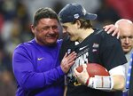 LSU head coach Ed Orgeron, left, celebrates a win against UCF with quarterback Joe Burrow, right, after a Fiesta Bowl NCAA college football game Tuesday, Jan. 1, 2019, in Glendale, Ariz. LSU defeated UCF 40-32. (AP Photo/Ross D. Franklin)