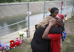 Christal McLemore is comforted by Debbie Robertson, left, and Takenna Triplett at a makeshift memorial at the spot where Miracle Crook, 3, and Tony Crook, 2, walked down to Mingo Creek at the Shoreline Apartments Wednesday, May 27, 2020. McLemore's grandaughter is the oldest sibling of the Crooks. The two young children were last seen days ago with their noncustodial mother, who was arrested after being questioned about their disappearance. (Mike Simons/Tulsa World via AP)