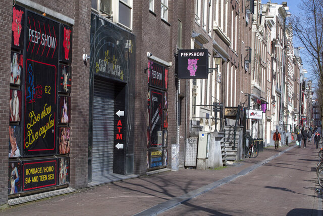 The narrow canal-side streets and alleys of Amsterdam's famed Red Light District, normally packed with tourists, were largely deserted Monday March 16, 2020, after the Dutch government ordered bars and restaurants closed and made a point of saying that the restrictions also cover sex clubs and weed-selling coffeeshops. For most people, the new coronavirus causes only mild or moderate symptoms, such as fever and cough. For some, especially older adults and people with existing health problems, it can cause more severe illness, including pneumonia. (AP Photo/Peter Dejong)