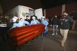 In this photo provided by Peru's Interior Ministry, health workers push the coffin of Abimael Guzman, founder and leader of the Shining Path guerrilla movement, at a crematorium in Callao, Peru, Friday, Sept. 24, 2021. The Peruvian government cremated Guzman on Friday, according authorities. (Rolly Reyna/Peruvian Interior Ministry via AP)