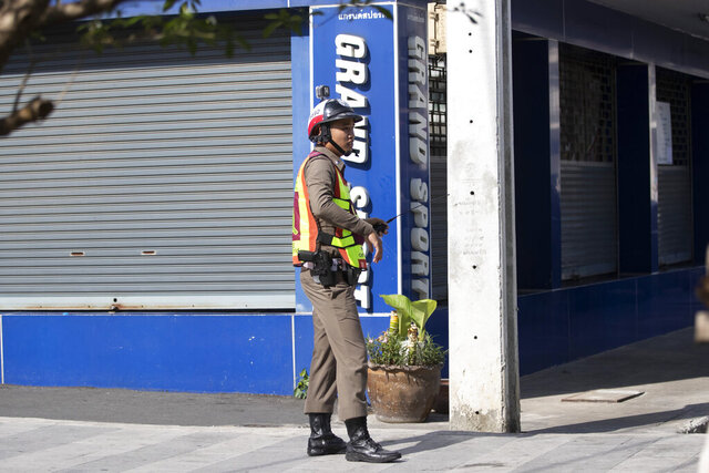 A Thai police officer stands near the site of a shooting in Bangkok, Thailand, Friday, Feb. 14, 2020. Multiple gunshots have been fired into the air by a man in the middle of the capital Bangkok, police said.  (AP Photo/Sakchai Lalit)