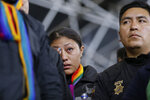 A policewoman, who was detained by anti-governments protesters, cries while standing on a stage at the Casa de Cultura, in Quito, Ecuador, Thursday, Oct. 10, 2019. Thousands of protesters staged anti-government rallies seeking to intensify pressure on Ecuador's president after a week of unrest sparked by fuel price hikes. (AP Photo/Fernando Vergara)