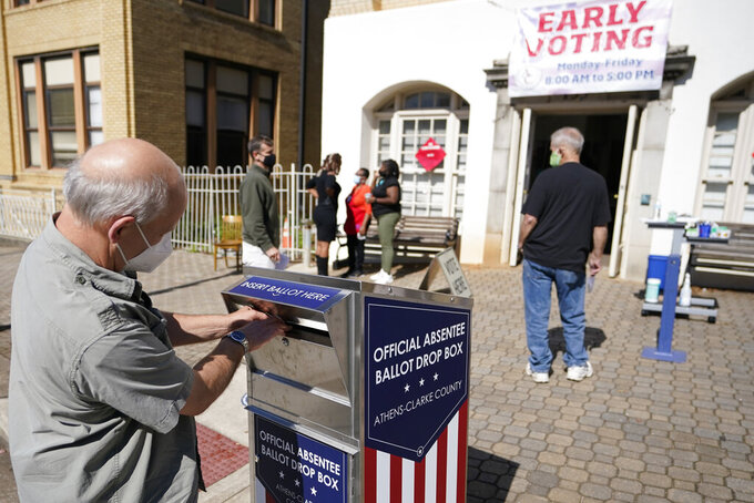 "FILE - In this Monday, Oct. 19, 2020 file photo, a voter submits a ballot in an official drop box during early voting in Athens, Ga. On Friday, April 2, 2021, The Associated Press reported on stories circulating online incorrectly asserting ""Georgia's new anti-voting law makes it a jail-time crime to drop off grandma's absentee ballot in a drop box."" But the election bill known as SB 202, signed into law on March 25, has an exception allowing people to drop off ballots on behalf of their relatives. It also allows a caregiver to deliver a completed ballot on behalf of a disabled person, or a jail employee to deliver a completed ballot on behalf of someone who is in custody. (AP Photo/John Bazemore)"