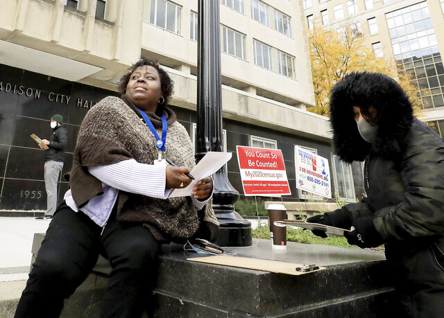Madison, Wis. residents Theola Carter, left, and Carrie Braxton fill out their ballots on the first day of the state's in-person absentee voting window for the Nov. 3 election outside the city's City-County Building Tuesday, Oct. 20, 2020. (John Hart/Wisconsin State Journal via AP)