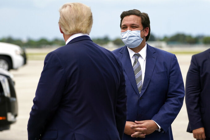 FILE - In this Sept. 8, 2020, file photo President Donald Trump greets Florida Gov. Ron DeSantis as he arrives at West Palm Beach International Airport in West Palm Beach, Fla. Now that the pandemic appears to be waning and DeSantis is heading into his reelection campaign next year, he has emerged from the political uncertainty as one of the most prominent Republican governors and an early White House front-runner in 2024 among Donald Trump's acolytes, if the former president doesn't run again. (AP Photo/Evan Vucci, File)
