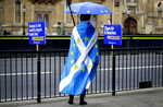 An anti-brexit campaigner stands opposite Parliament in London, Monday, Sept. 9, 2019. British Prime Minister Boris Johnson voiced optimism Monday that a new Brexit deal can be reached so Britain leaves the European Union by Oct. 31. (AP Photo/Kirsty Wigglesworth)