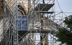 A man works on the scaffolding on the facade of the Notre Dame Cathedral in Paris, Thursday, April 18, 2019. Nearly $1 billion has already poured in from ordinary worshippers and high-powered magnates around the world to restore Notre Dame Cathedral in Paris after a massive fire. (AP Photo/Christophe Ena)