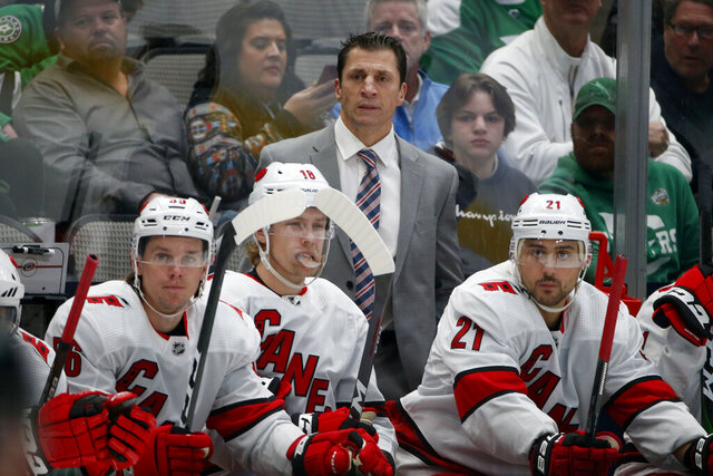 Carolina Hurricanes head coach Rod Brind'Amour watches his team play the Dallas Stars with left wing Erik Haula (56) center Ryan Dzingel (18) and right wing Nino Niederreiter (21) during the first period of an NHL hockey game in Dallas, Tuesday, Feb. 11, 2020. (AP Photo/Michael Ainsworth)