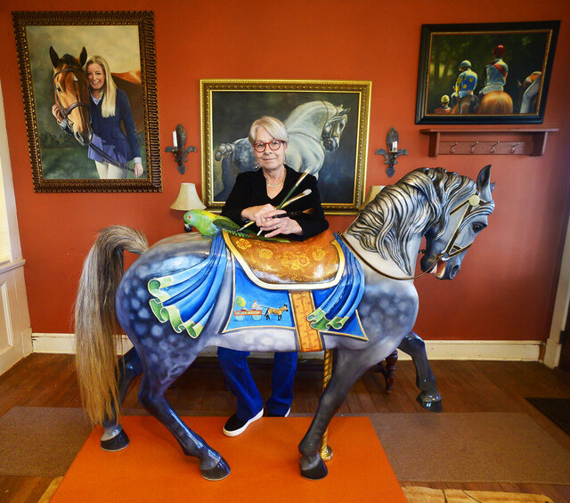 In this photo taken Dec. 3, 2019, artist Linda Luster stands in Rocky Ridge, Md., behind the carousel horse she recently painted. Some of her paintings hang on the wall. (Sam Yu/The Frederick News-Post via AP)