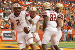 Boston College's AJ Dillon, left, celebrates with teammates after scoring a touchdown during the second quarter of an NCAA college football game against Boston College in Syracuse, N.Y., Saturday, Nov. 2, 2019. (AP Photo/Nick Lisi)