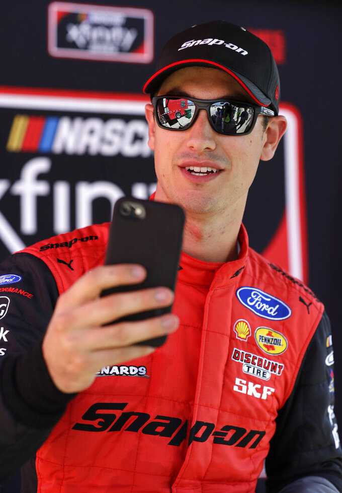 Joey Logano talks on the phone after qualifying on pole for the NASCAR Xfinity Series auto race at Chicagoland Speedway in Joliet, Ill., Saturday, June 29, 2018. (AP Photo/Nam Y. Huh)