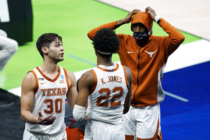 Texas' Brock Cunningham (30) and Kai Jones (22) leave the court after a loss to Abilene Christian in a college basketball game in the first round of the NCAA tournament at Lucas Oil Stadium in Indianapolis Sunday, March 21, 2021. (AP Photo/Mark Humphrey)