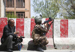 An Afghan Security personnel aims his weapon outside the Telecommunication Ministry during a gunfight with insurgents in Kabul, Afghanistan, Saturday, April 20, 2019. Afghan officials say an explosion has rocked the telecommunications ministry in the capital city of Kabul. Nasart Rahimi, a spokesman for the interior ministry, said Saturday the blast occurred during a shootout with security forces. (AP Photo/Rahmat Gul)