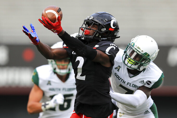Cincinnati wide receiver Jayshon Jackson (2) makes a catch against South Florida defensive back Mike Hampton (7) during the second half of an NCAA college football game, Saturday, Oct. 3, 2020, in Cincinnati. (AP Photo/Aaron Doster)