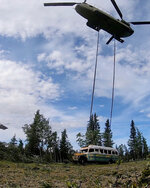 In this photo released by the Alaska National Guard, Alaska Army National Guard soldiers use a CH-47 Chinook helicopter to removed an abandoned bus, popularized by the book and movie