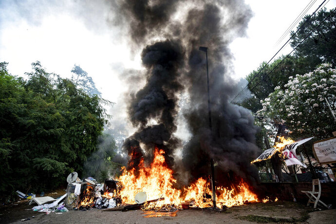 A barricade is on fire outside an abandoned school before being evicted, on the outskirts of Rome, Monday, July 15, 2019. Residents set fire early Monday to mattresses and other garbage to form a barrier and prevent riot police from entering the building but authorities doused the blaze and proceeded with the eviction. (Massimo Percossi/ANSA via AP)