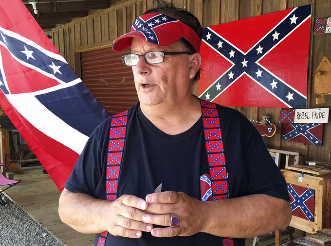"FILE - In this Aug. 17, 2017, file photo, Bob Castello, owner of the Dixie General Store, talks during an interview in Chulafinnee, Ala. Castello makes a living selling hundreds of rebel-themed shirts, hats, car accessories and more in an east Alabama county named for a Confederate officer, Gen. Patrick Cleburne. ""Business is very good right now,"" Castello said Monday, June 29, 2020. (AP Photo/Jay Reeves, File)"