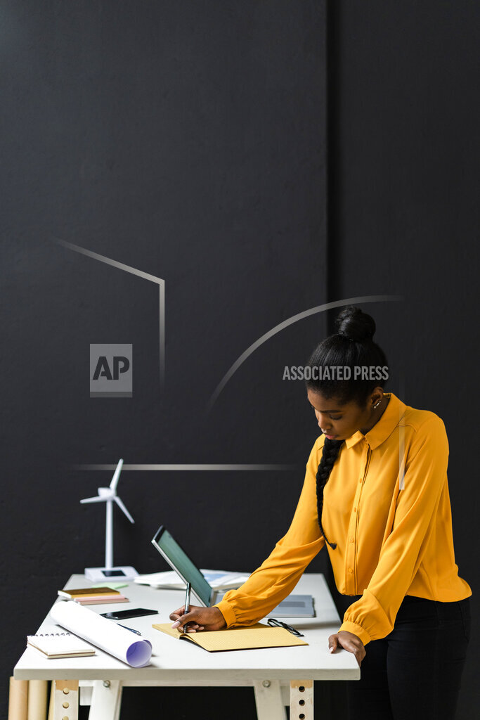 Dedicated businesswoman working in studio by black wall