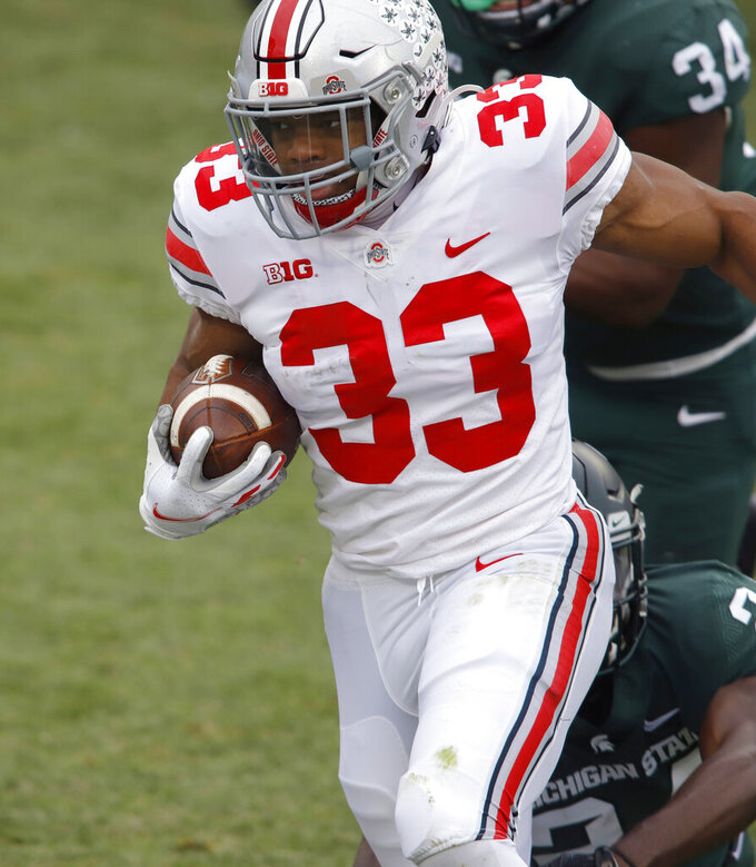 Ohio State's Master Teague III rushes against Michigan State during the first half of an NCAA college football game, Saturday, Dec. 5, 2020, in East Lansing, Mich. (AP Photo/Al Goldis)