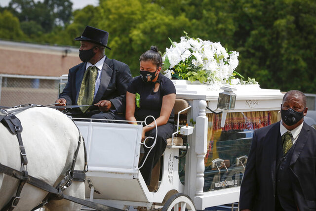 Lupe Guillen, the youngest sister of U.S. Army Specialist Vanessa Guillen rides on a horse draw carriage as they made a final lap around the Cesar Chavez High School track Friday, Aug. 14, 2020, in Houston. Guillen, who was last seen on April 22, was laid to rest nearly four months after she is said to have been killed by a fellow soldier at Fort Hood, a U.S. Army base in Texas. Mourners gathered at the high school where Guillen grew up playing soccer and dreaming of joining the military. (Steve Gonzales/Houston Chronicle via AP)
