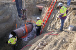 In this April 13, 2020, photo provided by TC Energy, construction contractors for TC Energy are seen installing a section of the Keystone XL crude oil pipeline at the U.S.-Canada border north of Glasgow, Mont. U.S. District Judge Brian Morris has struck down a nationwide permitting program for new oil and gas pipelines in a lawsuit against the controversial Keystone XL oil sands pipeline from Canada. (TC Energy via AP)
