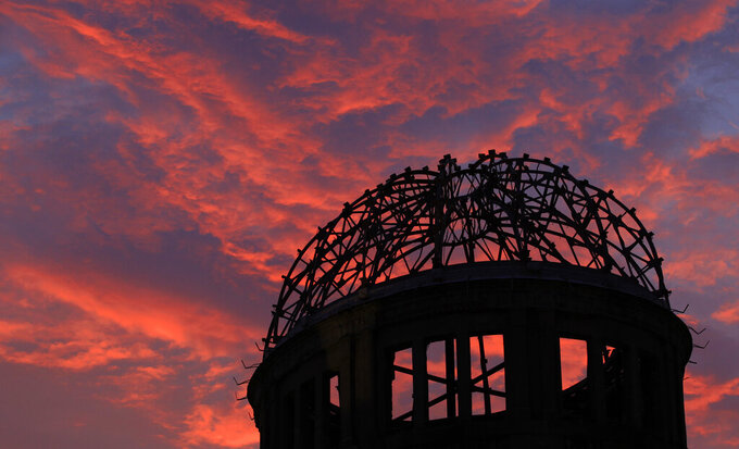 FILE - In this Aug. 5, 2013, file photo, the Atomic Bomb Dome is silhouetted at sunset in Hiroshima, western Japan. Many residents of Hiroshima welcome attention to their city from abroad, which IOC President Thomas Bach will bring when he visits on Friday, July 16. But Bach will also bring political baggage — as will his vice president John Coates when he visits Nagasaki the same day — that is largely unwelcome in two cities viewed as sacred by many Japanese. (AP Photo/Shizuo Kambayashi, File)