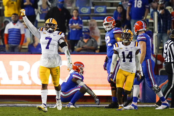 LSU safety JaCoby Stevens (7) and safety Maurice Hampton Jr. (14) celebrate after LSU stopped Florida on a fourth-and-goal at the 1-yard line during the first half of an NCAA college football game Saturday, Dec. 12, 2020, in Gainesville, Fla. (AP Photo/John Raoux)