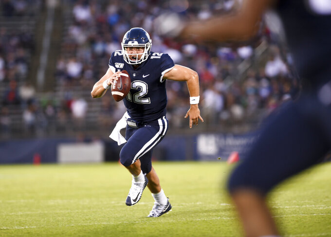 Connecticut quarterback Mike Beaudry (12) runs for a touchdown during the first half of the team's NCAA college football game against Wagner on Thursday, Aug. 29, 2019, in East Hartford, Conn. (AP Photo/Stephen Dunn)
