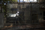 An employee wearing a protective face mask amid the new coronavirus pandemic, sweeps the patio of a closed restaurant in Bogota, Colombia, Tuesday, Jan. 5, 2021. Colombia's capital city is reimposing lockdown measures on Tuesday as COVID-19 infections rise around the country. (AP Photo/Ivan Valencia)