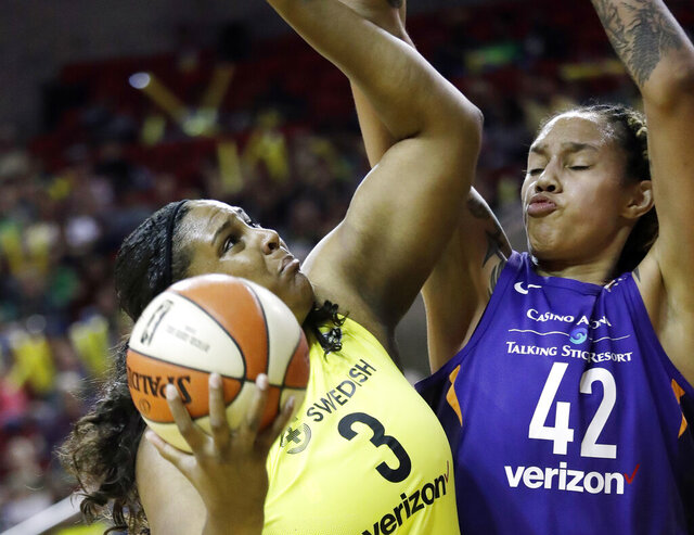FILE - In this Sunday, May 20, 2018, file photo, Phoenix Mercury's Brittney Griner (42) defends Seattle Storm's Courtney Paris (3) in the first half of a WNBA basketball game in Seattle. Former University of Oklahoma player Paris, who left Oklahoma with 20 NCAA Division I records, is returning to Oklahoma as an assistant coach. (AP Photo/Elaine Thompson, File)