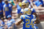 UCLA Bruins running back Zach Charbonnet (24) celebrates with wide receiver Kyle Philips (2) after scoring a touchdown during the first half of an NCAA college football game against the Hawaii Warriors Saturday, Aug. 28, 2021, in Pasadena, Calif. (AP Photo/Ashley Landis)