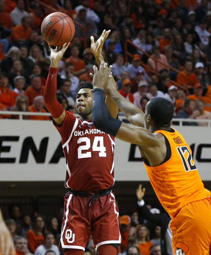 Oklahoma guard Jamal Bieniemy (24) shoots in front of Oklahoma State forward Cameron McGriff during the second half of an NCAA college basketball game in Stillwater, Okla., Wednesday, Jan. 23, 2019. (AP Photo/Sue Ogrocki)