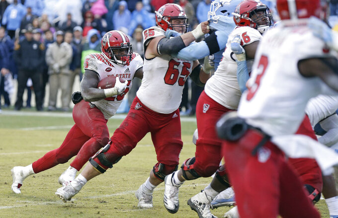 North Carolina State's Reggie Gallaspy II (25) lines up behind a block by center Garrett Bradbury (65) during overtime in an NCAA college football game against North Carolina in Chapel Hill, N.C., Saturday, Nov. 24, 2018. Gallaspy scored the game-winning touchdown on the play. North Carolina State won 43-28. (AP Photo/Gerry Broome)