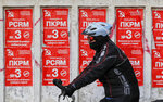 A man rides a bicycle by electoral posters advertising the Communist party in Chisinau, Moldova, Thursday, Feb. 21, 2019, ahead of parliamentary elections taking place on Feb. 24. Moldova's president says the former Soviet republic needs good relations with Russia, amid uncertainty about the future of the European Union. (AP Photo/Vadim Ghirda)
