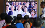 People watch a TV screen showing a live broadcast of South Korean President Moon Jae-in, center left, and his wife Kim Jung-sook during a ceremony to celebrate the Korean Liberation Day, marking the 74th anniversary of Korea's liberation from the Japanese colonial rule, at the Seoul Railway Station in Seoul, South Korea, Thursday, Aug. 15, 2019. The signs read: