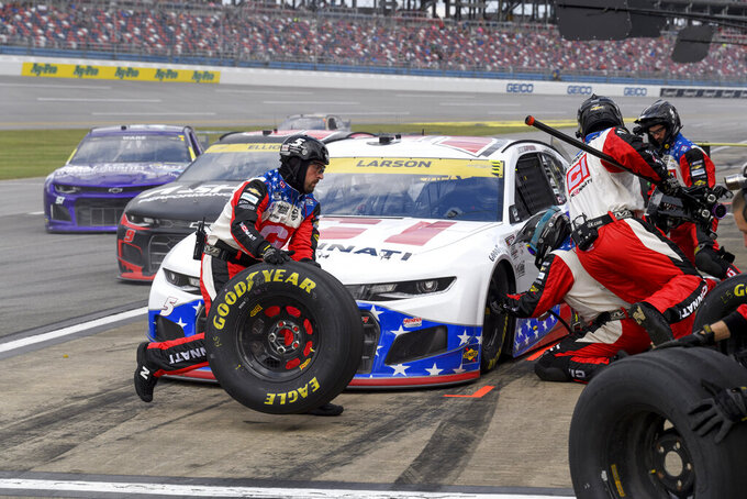Crew members tend to the car driven by Kyle Larson during a pit stop in a NASCAR Cup series auto race Monday, Oct. 4, 2021, in Talladega, Ala. (AP Photo/John Amis)