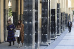 People walk between damaged pillars of Beirut Souks, a 100,000 sq. meters gigantic shopping mall, in Beirut, Lebanon, Friday, Jan. 24, 2020. As cement barricades come up across the capital, blocking the path to major government buildings, Lebanese protesters vowed to continue taking to the street on the 100-day anniversary of the anti-government protests. (AP Photo/Hassan Ammar)
