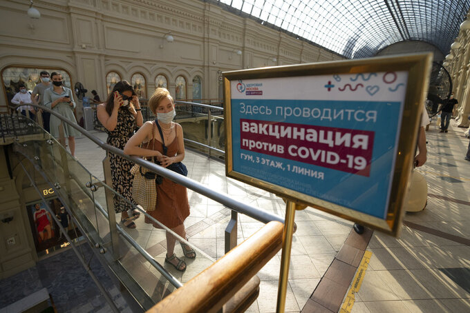 People stand in line to get a coronavirus vaccine at a center in the GUM, State Department store, in Red Square in Moscow, Russia, Tuesday, June 22, 2021. An ambitious plan of vaccinating 30 million Russians by mid-June against the coronavirus has fallen short by a third, and the country has started to see a surge in daily new infections. (AP Photo/Pavel Golovkin)