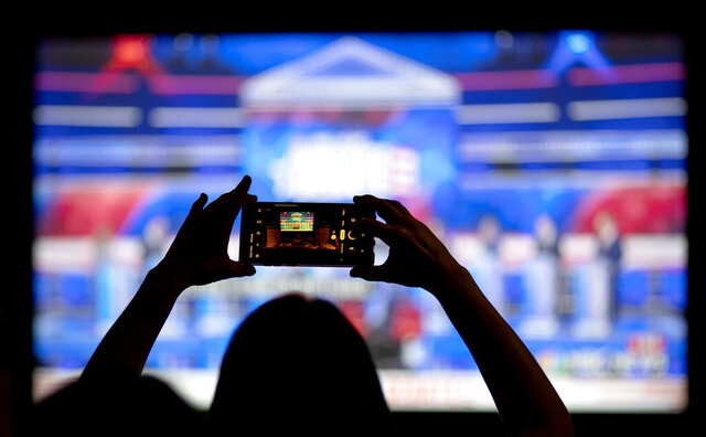 FILE - In this June 27, 2019, file photo, a woman takes a photo of the television while watching a Democratic presidential debate at a watch party in Atlanta. The Democratic race for the White House has been marked by online infighting and unsubstantiated allegations of election rigging. (AP Photo/David Goldman, File)