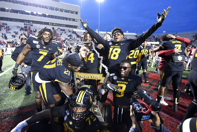 Missouri players celebrate with the Battle Line trophy after defeating Arkansas in an NCAA college football game, Friday, Nov. 29, 2019 in Little Rock, Ark. (AP Photo/Michael Woods)