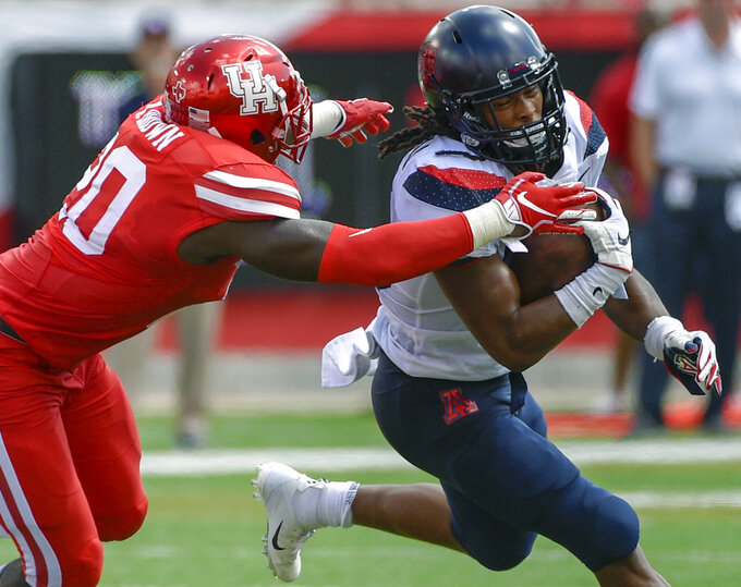 Arizona running back Gary Brightwell, right, is tackled by Houston linebacker Roman Brown during the first half of an NCAA college football game, Saturday, Sept. 8, 2018, in Houston. (AP Photo/Eric Christian Smith)