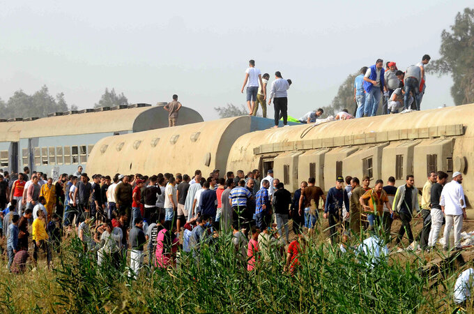 People gather at the site where a passenger train derailed injuring at least 100 people, near Banha, Qalyubia province, Egypt, Sunday, April 18, 2021. At least eight train wagons ran off the railway, the provincial governor's office said in a statement. (AP Photo/Tarek Wagih)