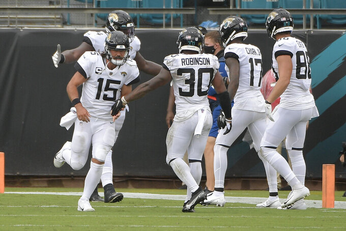 Jacksonville Jaguars quarterback Gardner Minshew (15) celebrates after throwing a touchdown pass to wide receiver D.J. Chark (17) during the first half of an NFL football game against the Indianapolis Colts, Sunday, Sept. 13, 2020, in Jacksonville, Fla. (AP Photo/Phelan M. Ebenhack)