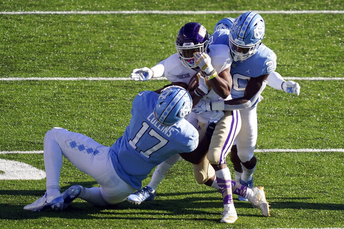 Western Carolina wide receiver Daquan Patten is tackled by North Carolina linebacker Chris Collins (17) and defensive back Tony Grimes (20) during the second half of an NCAA college football game in Chapel Hill, N.C., Saturday, Dec. 5, 2020. (AP Photo/Gerry Broome)