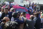Supporters of Pakistan's ailing former prime minister Nawaz Sharif surrounds his vehicle at airport in Lahore, Pakistan, Tuesday, Nov. 19, 2019. Sharif has arrived to board a special plane after a court permitted him to leave the country for four weeks abroad for medical treatment. (AP Photo/K.M. Chaudary)
