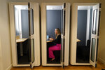 Kelly Soderlund works in a quiet booth at the TripActions office in San Francisco, Friday, Aug. 27, 2021. Switching to a hybrid work model is ideal for people like Soderlund, a mother of two young children who works in offices in San Francisco and Palo Alto, California, for TripActions, which has about 1,200 employees worldwide. She couldn't wait to return when TripActions partially reopened its offices in June, partly because she missed seeing her co-workers but also because she missed the built-in buffer that her roughly one-hour commute provided between her personal and professional life. (AP Photo/Eric Risberg)